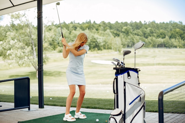 Piękna dziewczyna bawić się golfa na polu golfowym