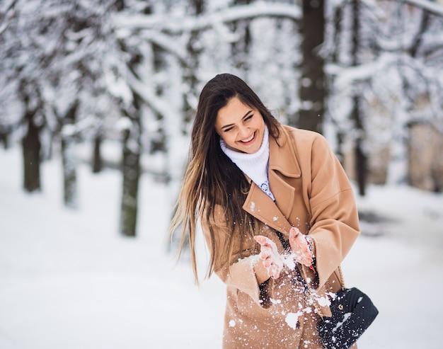 Piękna dziewczyna bawić się z śniegiem