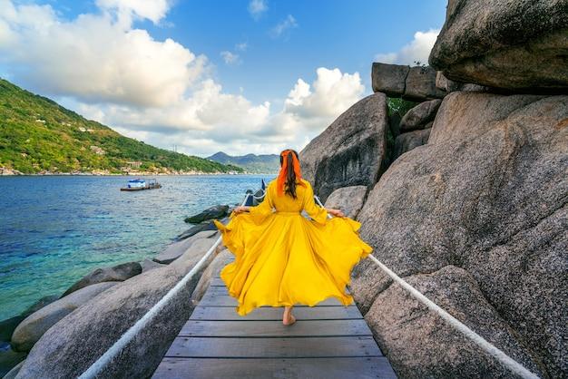 Piękna dziewczyna biegnie na drewnianej ścieżce na wyspie koh nang yuan w pobliżu wyspy koh tao, surat thani w tajlandii