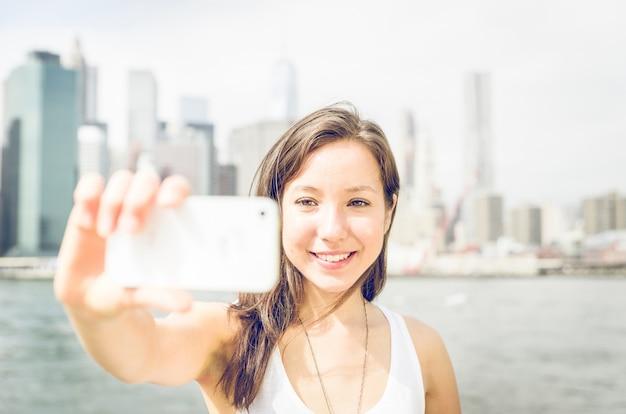 Piękna dziewczyna bierze selfie z mądrze telefonem na nowym york mieście