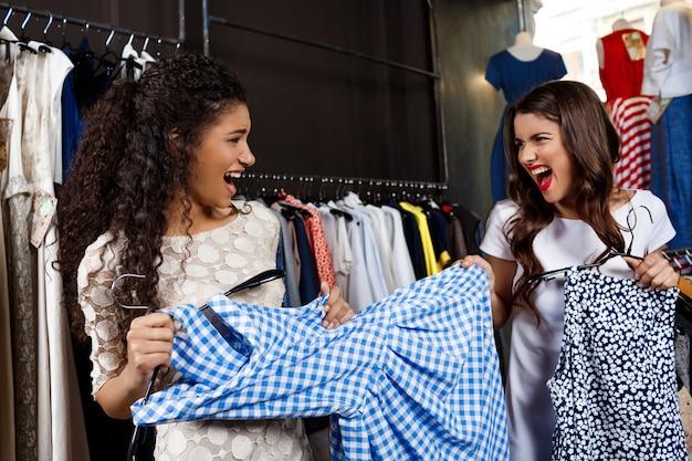 Piękna dziewczyna bierze suknię od innego w centrum handlowym.