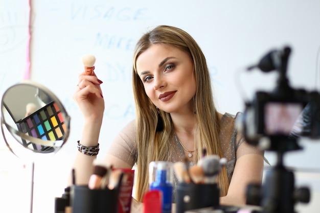 Piękna dziewczyna blogger nagrywanie porad kosmetycznych vlog. blog wideo blond kobieta. lustro, sprzęt visagist i produkt kosmetyczny na toaletce. modny styl życia vlogger girl social