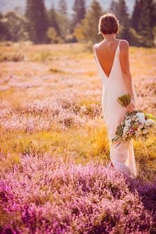 Piękna dziewczyna chodzi wzdłuż pola
