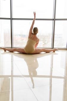 Piękna dziewczyna choreograf w pobliżu okna.
