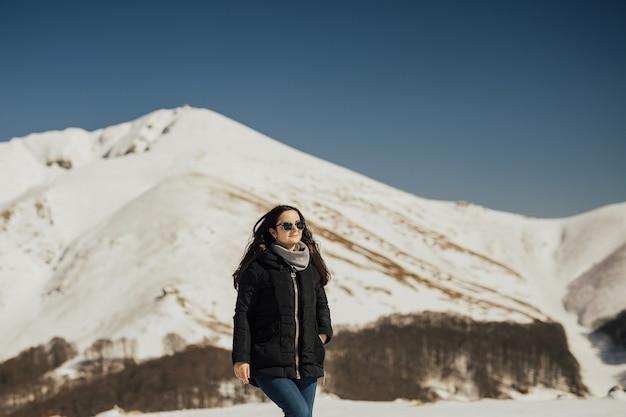Piękna dziewczyna, ciesząc się słońcem w zimowy dzień w górach alp.