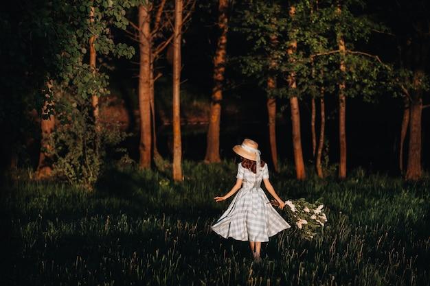 Piękna dziewczyna ciesząc się zapachem bzu w letni dzień. koncepcja aromaterapii i wiosny. ładna dziewczyna, piękna kobieta w niebieskiej długiej sukience vintage stoi w liliowym ogrodzie. prace ogrodowe.