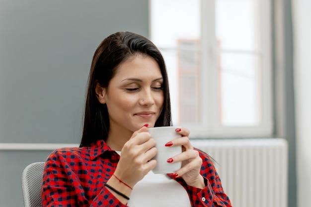 Piękna dziewczyna cieszy się pierwszą poranną kawę w biurze.