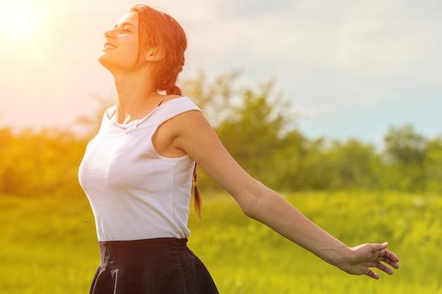 Piękna dziewczyna cieszy się słońce z jej rękami szeroko rozpościerać w polu przeciw niebu