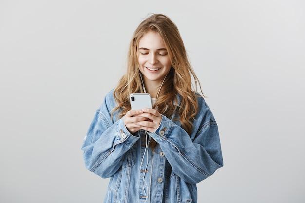 Piękna dziewczyna college'u sms-y, wiadomości i słuchanie muzyki w słuchawkach