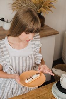 Piękna dziewczyna cukiernik lub gospodyni domowa trzymająca talerz z eklerami kurs gotowania lub cukiernia