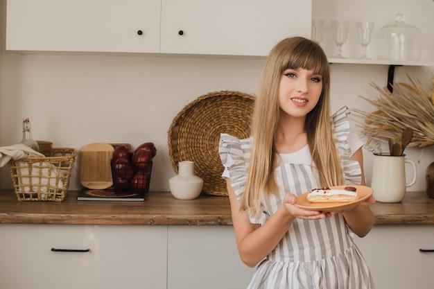 Piękna dziewczyna cukiernik lub gospodyni domowa w kuchni trzyma talerz z eklerami