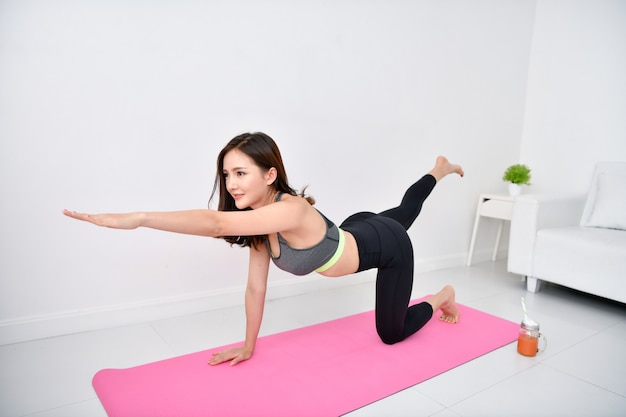 Piękna dziewczyna ćwiczy w swoim domu.