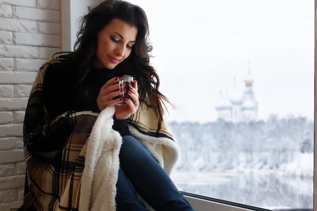Piękna dziewczyna czeka na miłość siedzi na parapecie owinięta kocem i pije herbatę