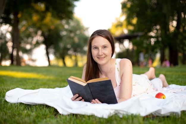 Piękna dziewczyna czyta książkę leżąc na zielonej trawie z matą w parku