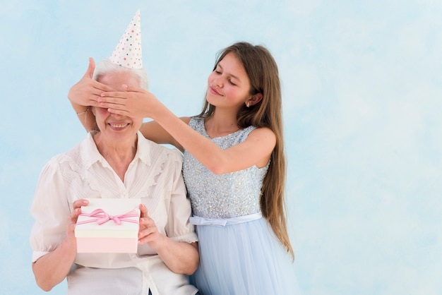 Piękna dziewczyna daje zaskoczony prezent, zakrywając oczy babci
