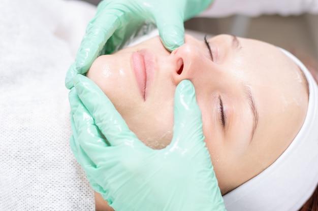 Piękna dziewczyna dostaje peeling do twarzy. pojęcie zdrowia skóry. salony piękności. różne środki przekazu