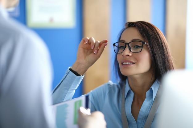 Piękna dziewczyna dostosowuje okulary w biurze zbliżenie