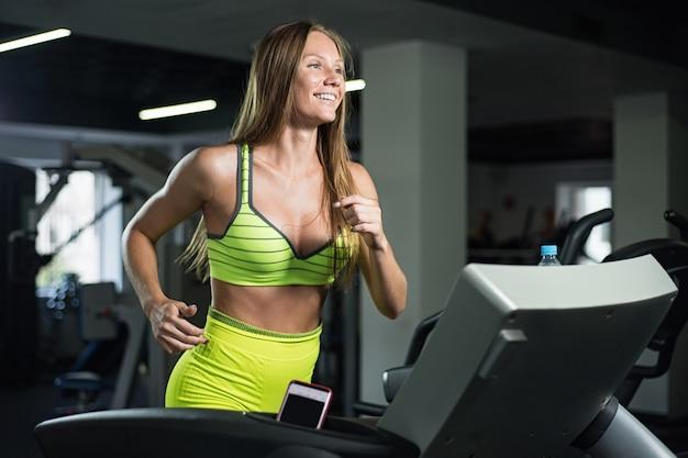 Piękna dziewczyna działa na bieżni w siłowni, pojęcie zdrowego stylu życia