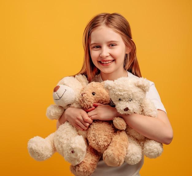 Piękna dziewczyna dziecko z trzema misiami na białym tle na żółtym tle z copyspace portret...