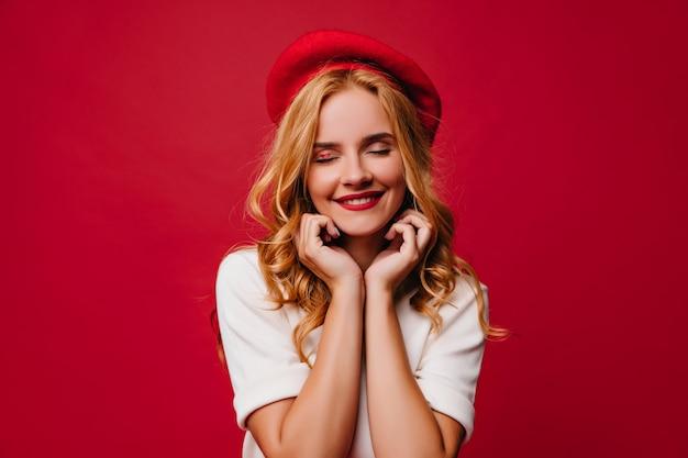 Piękna dziewczyna europejskiej w berecie francuskim, uśmiechając się. portret błogiej blondynki pani w dobrym nastroju.