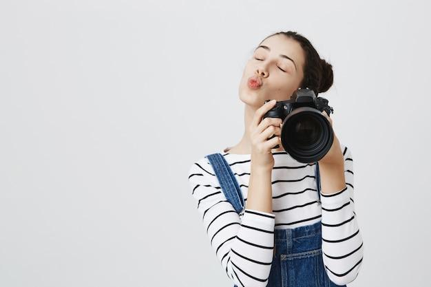 Piękna dziewczyna fotograf zamyka oczy i dąsa, robi zdjęcia swoim aparatem