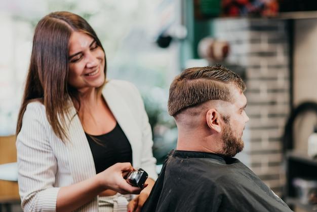 Piękna dziewczyna fryzjer tnie brodatego mężczyznę w salonie