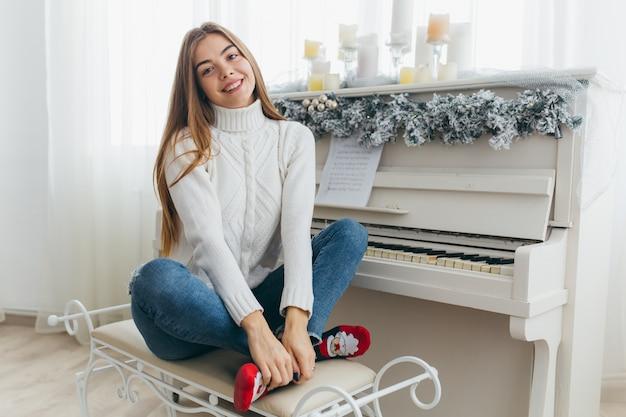 Piękna dziewczyna gra na pianinie w boże narodzenie.