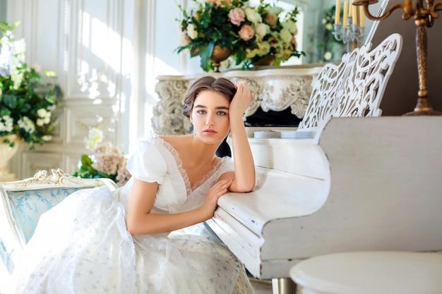 Piękna dziewczyna gra na pianinie, w pięknej sukience we wnętrzu