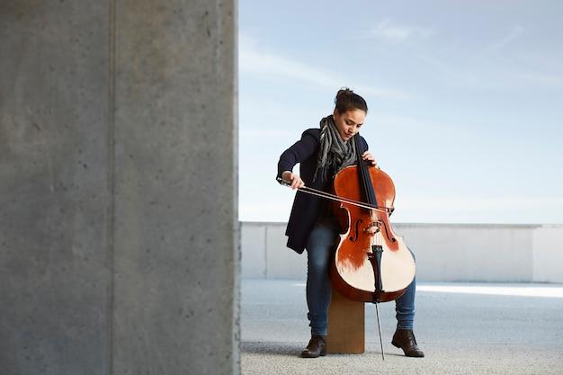 Piękna dziewczyna gra z pasją na wiolonczeli w konkretnym otoczeniu