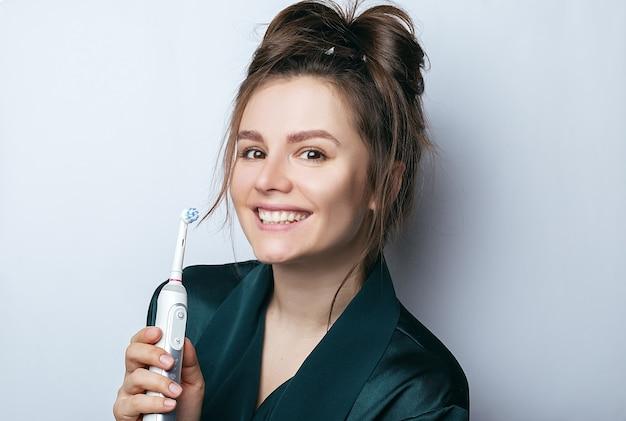Piękna dziewczyna i elektryczna szczoteczka do zębów