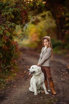 Piękna dziewczyna i piesek na spacer w jesiennym parku