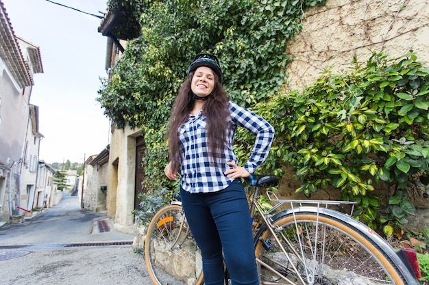 Piękna dziewczyna i rower w wąskiej uliczce