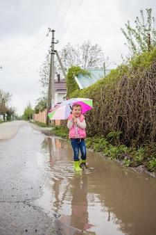 Piękna dziewczyna idzie przez ogromne kałuże z otwartym parasolem i gumowymi butami.