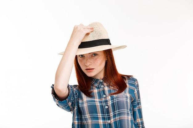 Piękna dziewczyna imbir w kapeluszu na białej ścianie.