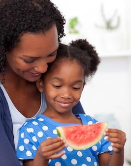 Piękna dziewczyna jedzenie arbuza z matką