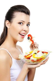 Piękna dziewczyna jedzenie warzyw - na białym tle