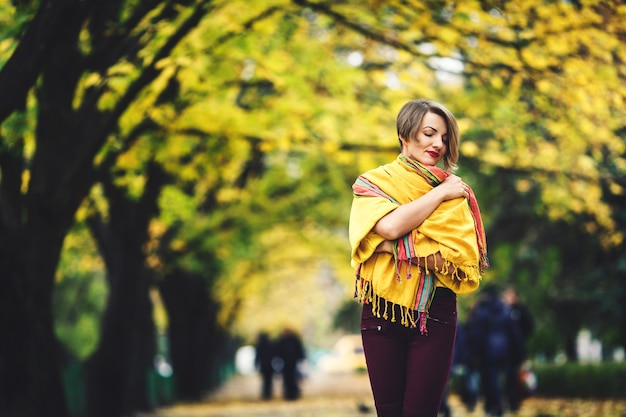 Piękna dziewczyna jesienią stoi na ulicy, owinięta żółtą chustką.