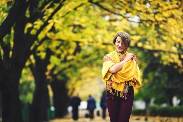 Piękna dziewczyna jesienią stoi w parku owinięta żółtą chustką i uśmiecha się.