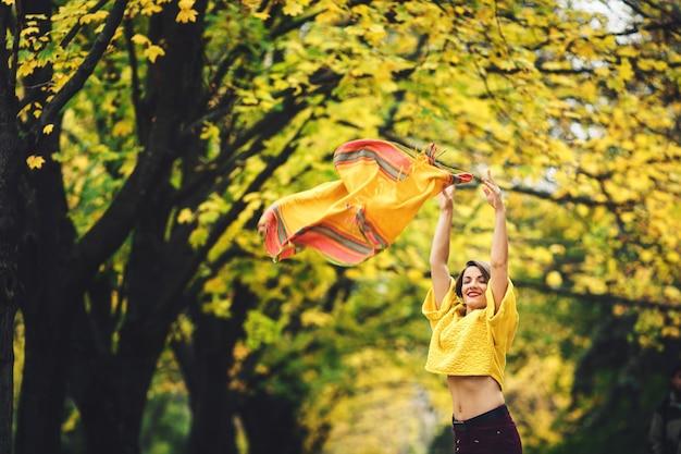 Piękna dziewczyna jesienią w parku rzuca żółtą chustkę i uśmiecha się.