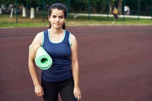 Piękna dziewczyna jest gotowa do jogi na stadionie sportowym. młoda kobieta patrzy w bok