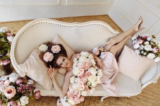 Piękna dziewczyna jest na kanapie z kwiatami. niesamowita dziewczyna z kwiatami w widoku z góry.