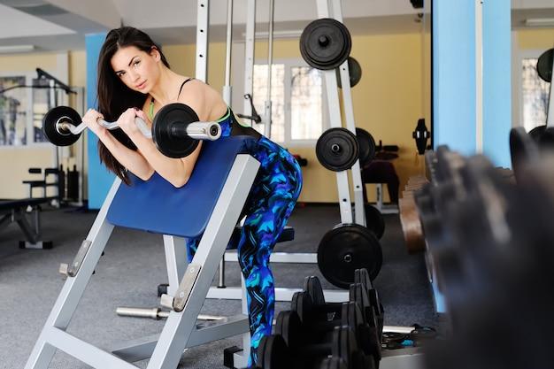 Piękna dziewczyna jest zaangażowana w siłowni