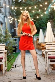 Piękna dziewczyna kaukaski z czerwonymi ustami makijaż w restauracji. piękna seksowna blond kobieta w restauracji kawiarni kusząca dziewczyna w czerwonej sukience fryzurę i makijaż jeść deser. moda uroda szczupła modelka