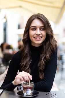 Piękna dziewczyna kawie w kawiarni na świeżym powietrzu