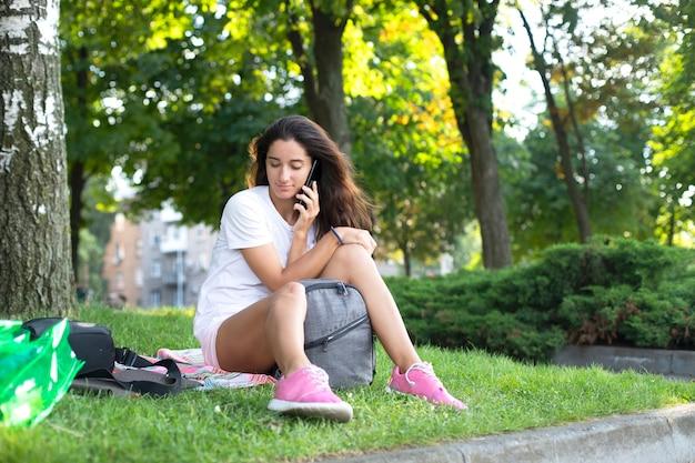 Piękna dziewczyna komunikuje się przez telefon. na zewnątrz, dziewczyna siedzi na trawie