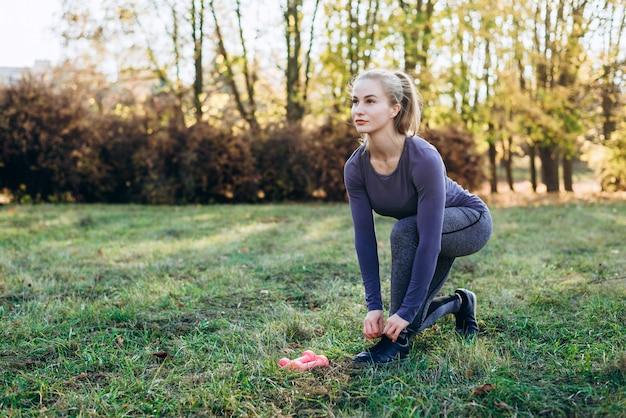 Piękna dziewczyna koronki buty w parku, patrząc w przyszłość.