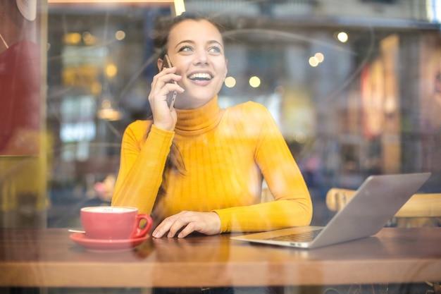 Piękna dziewczyna ma rozmowę telefonicza podczas gdy siedzący w kawiarni
