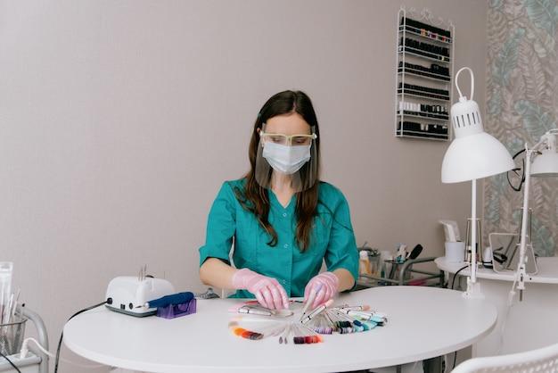 Piękna dziewczyna manikiurzystka w gabinecie kosmetycznym. koncepcja manicure, pedicure i urody. manikiurzystka siedzi w miejscu pracy w salonie paznokci
