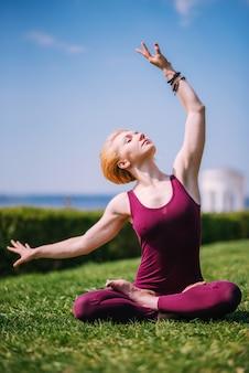 Piękna dziewczyna medytuje w pozycji lotosu, siedząc na trawie w słoneczny dzień