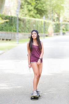 Piękna dziewczyna mieszanej rasy łyżwiarstwo w parku
